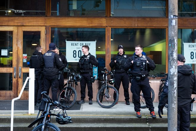Seven police stand in front of Seattle Central's bookstore, talking.