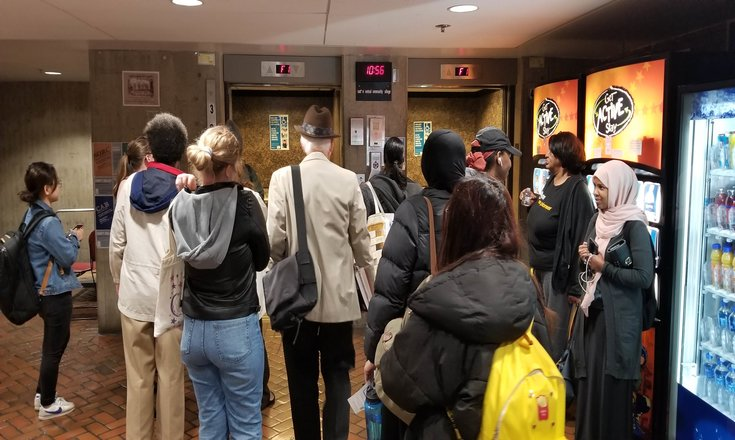 Students and faculty linger while main elevators are out of service following the most recent evacuation drill.