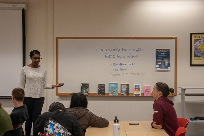"Kimberly Tate Malone introducing Gatsby & Pittman - on the board behind them is written ""Living in a Non-binary World - LGBTQ+ issues on campus"""