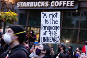 "A sign reads, ""A riot is the language of the unheard"""