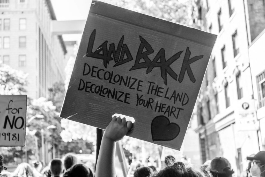 """A protestor holds a sign that reads """"Land Back; Decolonize the Land; Decolonize Your heart"""""""