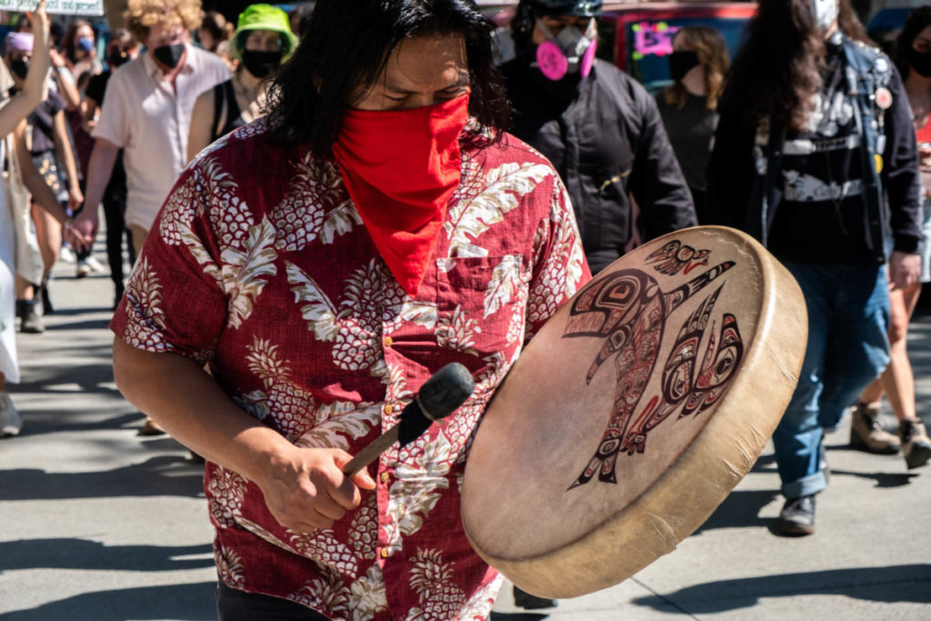 A protestor beats a native drum toward the front of the march