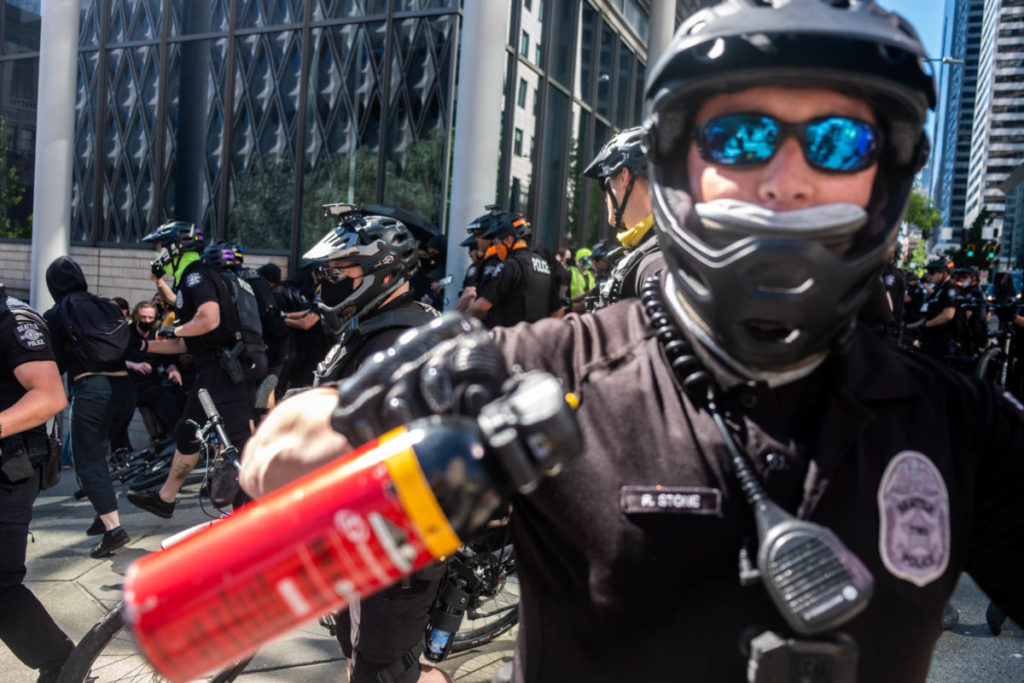 An SPD officer threatens protesters with pepper spray moments after dozens of policemen rode their bikes into the march, tackling and arresting several people