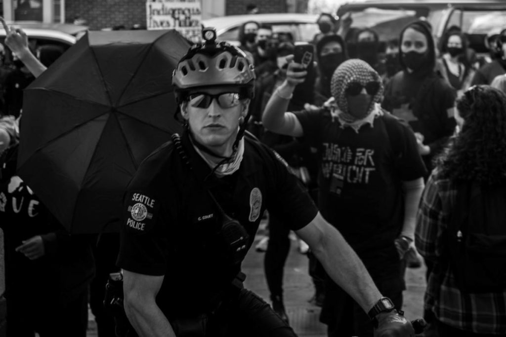A police officer looks directly into the camera as he and fellow officers try to direct and restrain the crowd of marchers