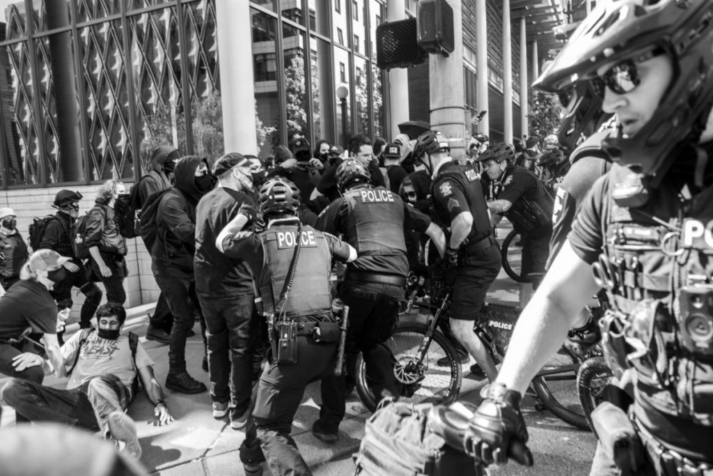 Police officers ride their bikes into the march, tackling and arresting several protesters