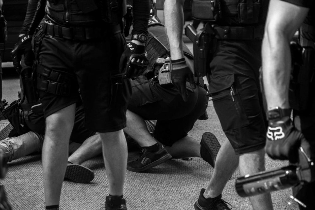 Police officers tackle and immobilize a protester on 4th Avenue