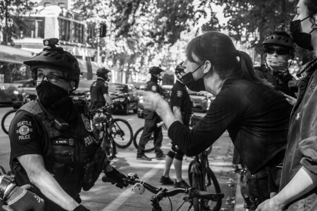 A protestor shouts vehemently toward a police officer who diverts their attention in another direction
