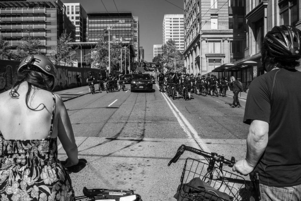 Two members of the bike brigade march look onward toward dozens of incoming policemen