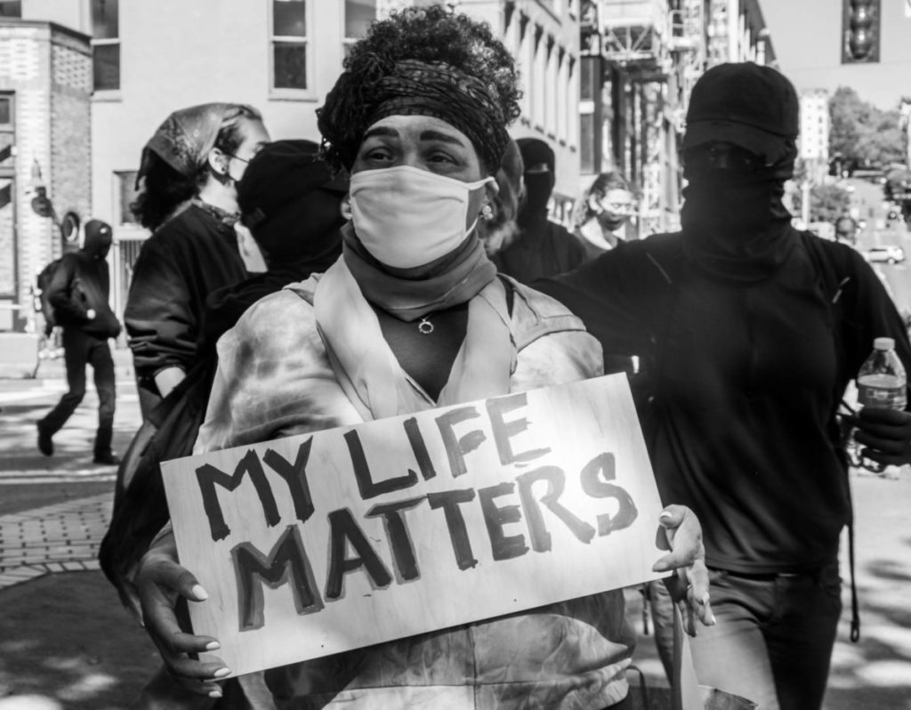"""A woman stands holding a """"My Life Matters"""" sign on the street corner of 2nd Avenue and Washington Street, moments after the march came to a close"""