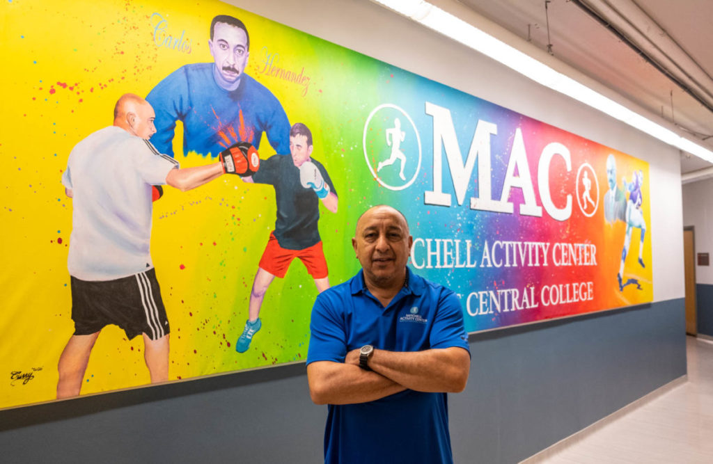 Hernandez in front of the mural commissioned in his honor