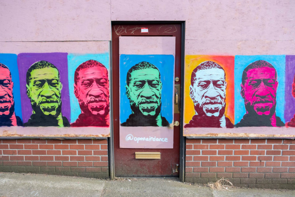 In the wake of George Floyd's murder and subsequent protests, Seattle's International District participated in a community-wide mural project, painting a variety of Black Lives Matter-themed artwork over the boarded up windows of many local businesses that were forced to close their doors due to theft and vandalism.
