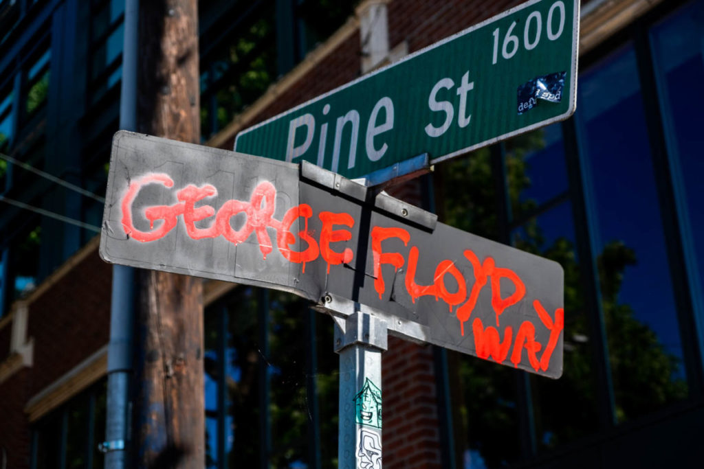 """After the formation of CHAZ, protestors painted """"George Floyd Way"""" over the 11th Avenue street sign.  11th Avenue and Pine Street became the epicenter of Seattle protests before the Seattle Police Department abandoned the East Precinct and subsequent formation of CHAZ."""